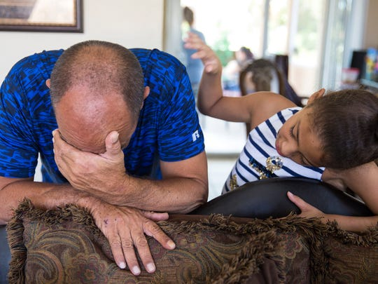 Francisco Moreno cries and is comforted by his granddaughter Elizabeth on Monday, Sept. 18, 2017, while remembering his son Yusdel Moreno Iglesias, who died of carbon monoxide poisoning the week before.