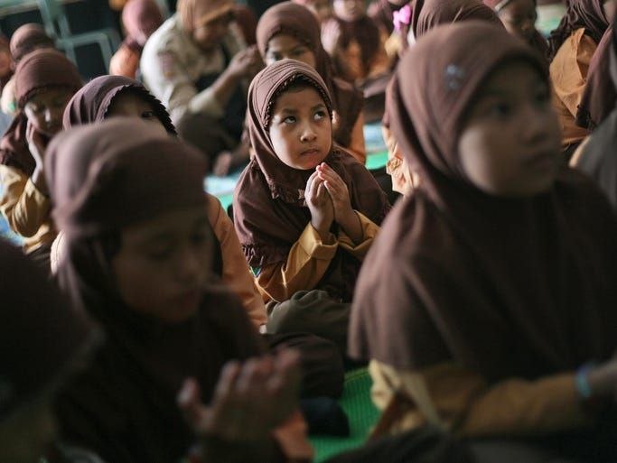 Students pray for the passengers aboard missing Malaysia Airlines Flight 370 during a class at an elementary school in Medan, North Sumatra, Indonesia.