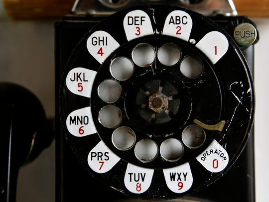A vintage rotary pay telephone hangs in the HC Sinclair