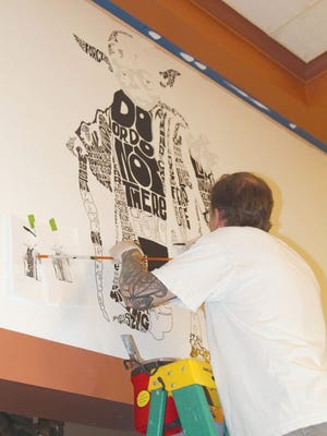"""Local artist Trey Everett a while back created a Grand Theatre sign/logo as part of the unveiling of the historic theater's upgraded marquee. Now, the artist who specializes in """"calligrams"""" - in which words are prominently featured in the image - is adding a trio of drawings on the wall above the lobby. Using paint as well as pen, he's shown here working on a calligram of Yoda from Star Wars, with all of the featured words being things Yoda has said in the Star Wars movings. On the left will be a Scooby-Doo drawing, and on the right will be a drawing of Batman. Everett said he didn't know if all three would be finished by the Grand Theatre's reopening on June 19. He also acknowledged that finding Scooby-Doo words and phrases will be far more challenging than incorporating things Yoda and Batman have said."""
