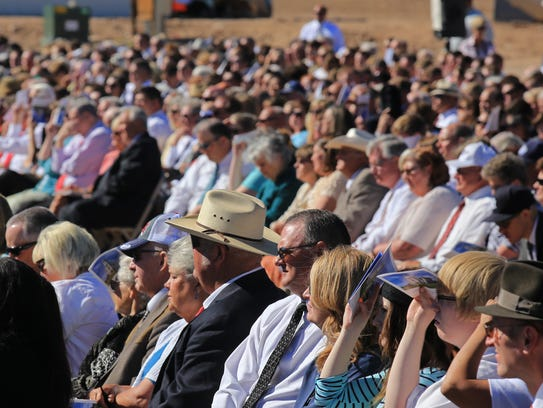 A crowd of hundreds sits in the bright sun Saturday