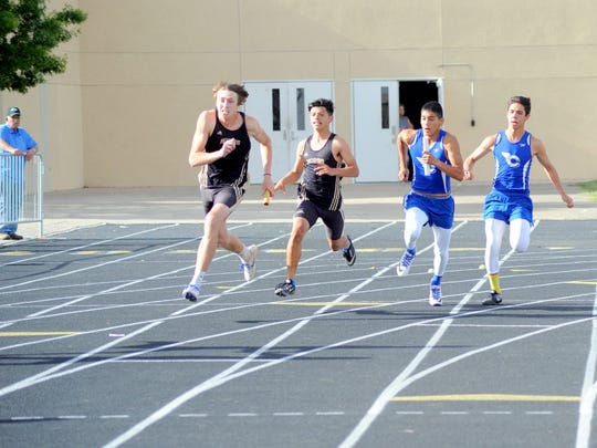 Carlsbad's Carlos Pedroza hands off to Xander Elizondo in the boys 400-meter relay Tuesday at Hobbs. The Cavemen won that event with a time of 43.38 seconds.