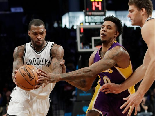 Brooklyn Nets' Sean Kilpatrick, left, drives past Los Angeles Lakers' Nick Young, center, as teammate Brook Lopez, right, watches during the second half of an NBA basketball game Wednesday, Dec. 14, 2016, in New York. The Nets won 107-97. (AP Photo/Frank Franklin II)