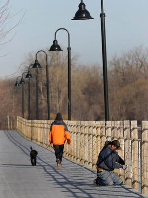 James Steen, an employee with Janke Contractors, works Tuesday along the Fox Cities Trestle Trail in Menasha.