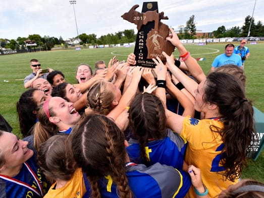 Bloomfield Hills Marian players raise the trophy and