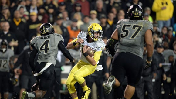 Oct 3, 2015; Boulder, CO, USA; Oregon Ducks quarterback Taylor Alie (12) carries in the second quarter against the Colorado Buffaloes at Folsom Field. Mandatory Credit: Ron Chenoy-USA TODAY Sports
