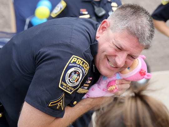 Lance Duffy, with the Gates Police Department, gives a little girl's doll a hug in July 2016 at the Gates Walmart where officers came out to bond with the community.