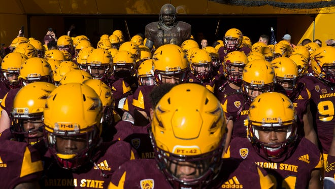 Arizona State players walk by the Pat Tillman statue before playing Arizona on Nov. 25, 2017 during the 91st Annual Territorial Cup in Tempe, Ariz.