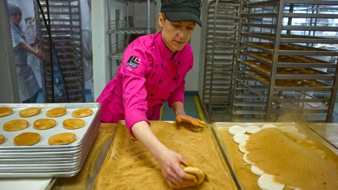 Liz Holtz, owner of Liz Lovely, works on coating cinnamon sugar cookies on the production line at her bakery in Waitsfield. Liz Lovely specializes in making vegan, gluten-, and GMO-free cookies.