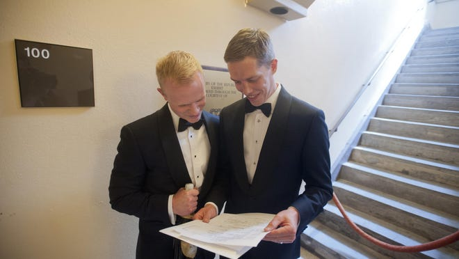 Benjamin Moore, left, joins his new husband, Tadd Roberts, in looking over their marriage license just outside the door of the Jefferson County Clerk's office on Friday. But clerks in at least five Kentucky counties are refusing to issue marriage licenses to any couples to avoid having to grant them to gay and lesbian partners.