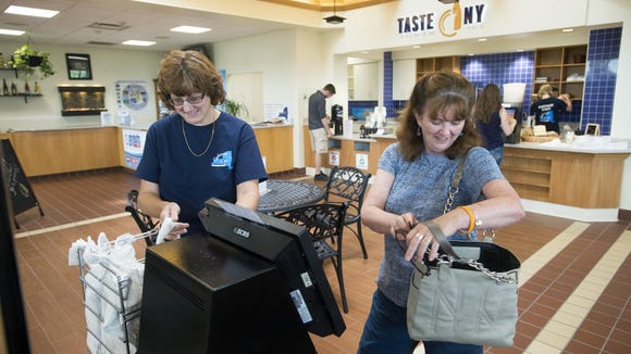 Robin Elliott Heacock, of Palm, Pennsylvania, right, uses the self-checkout machine to buy water, flax seed crackers and veggies with tomato hummus while Taste NY employee Andrea Braun helped bag July 7 at Taste NY in Kirkwood.