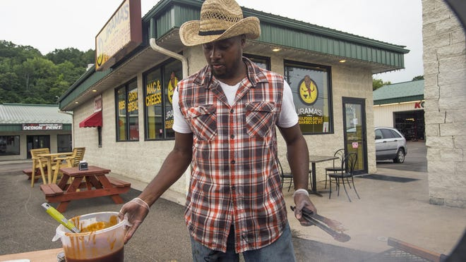 Jamar Johnson, owner of Jrama's Soulfood Grille & Barbecue Pit cooks barbecue chicken in front of his restaurant on Thursday.
