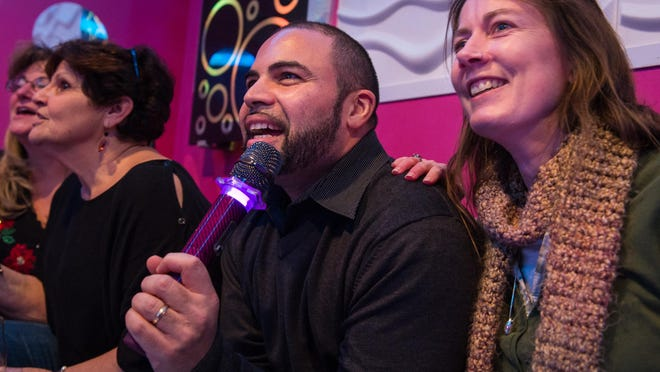 Corey Robinson, left, and Bethany Martin sing in a private lounge at Revolution Karaoke in Henrietta.