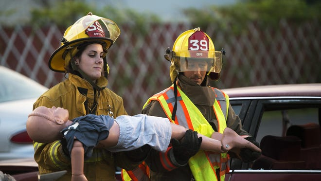 Miranda Currier, 19, helps remove a dummy from a mock car crash during a training exercise.