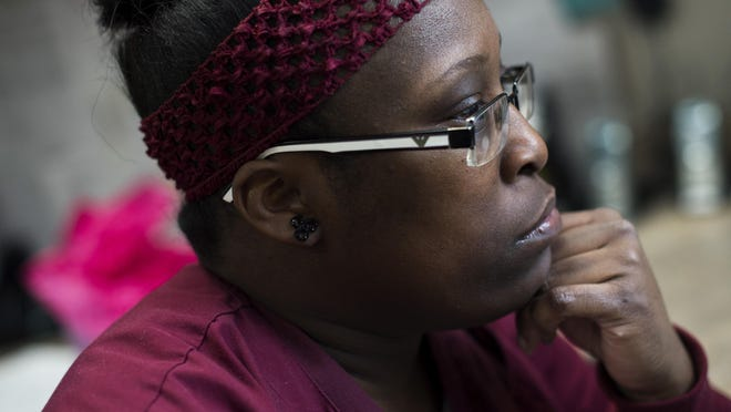 Nedra Smith, a patient care technician and graduate of the Detroit At Work healthcare training program, works on charts and records at St. John Hospital in Detroit. Detroit At Work connects Detroit residents to a free training program in certain career paths.