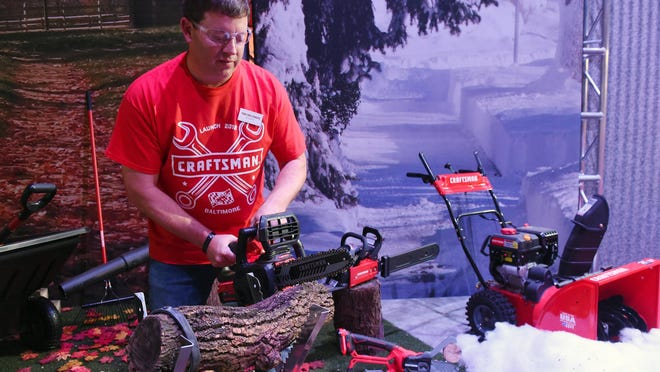 Todd Snellenburg, vice president of global licensing, shows off the Craftsman chainsaws on Thursday at the Craftsman Garage in Middle River, Md.