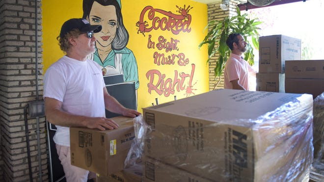 Rodney Mayo (left) moves boxes of food containers into the kitchen as Howley's sets up as a food distribution center March 21, 2020 providing free meals to several local charities, any laid off hospitality worker and of course our Subculture family. Food bags include a roll of toilet paper.