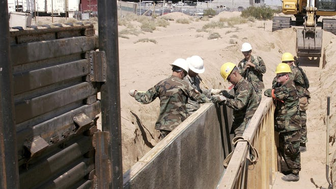 Utah National Guard troops from the 116th Construction Equipment Support Company prepare to extend a wall along the U.S. border June 5, 2006, in San Luis, Ariz. The soldiers are the first National Guard unit along the border as part of Operation Jump Start from May 2006 to July 2008.