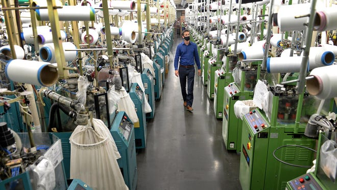 Jordan Schindler, founder and CEO of Nufabrx, walks through a row of machines producing Theramasks at the Bossong Medical plant in Asheboro on July 16.