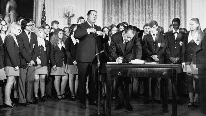 """President Richard Nixon signs the Constitution's newest amendment which guarantees 18-year-olds the right to vote in all elections. Robert Kunzig, general services administrator, waits to certify officially ratification of the 26th amendment. The signing took place Sunday, July 4, 1971 in East Room of the White House in Washington. Paul Larimer of Concord, Calif. , a member of the singing group """"Young Americans"""" also signed the amendment."""