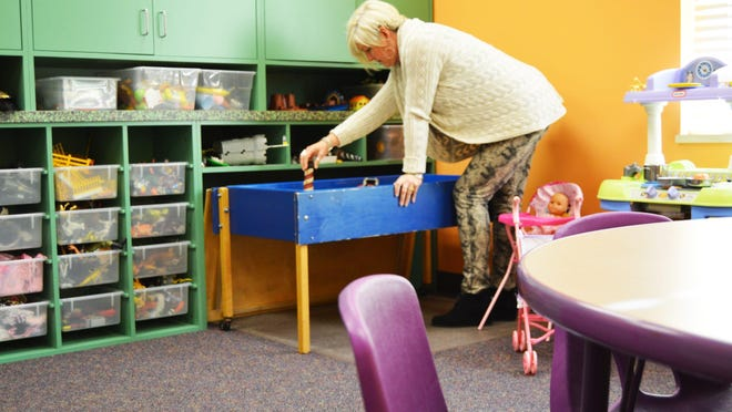 Karen Grissen, intake coordinator at Children's Advocacy Center, puts a few toys in the sand table in the center's play therapy room in 2014. The center has seen a dramatic increase in cases since Gov. Gretchen Whitmer's stay-home order was lifted and children returned to school in September 2020.