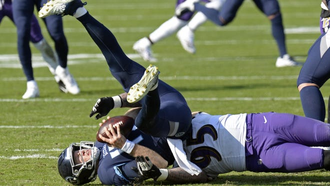 Tennessee Titans quarterback Ryan Tannehill (17) is sacked by Baltimore Ravens defensive end Derek Wolfe (95) for a 7-yard loss in the first half of an NFL wild-card playoff football game Sunday, Jan. 10, 2021, in Nashville, Tenn.