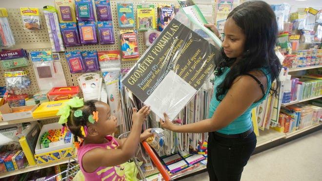 Seneca High geometry teacher Tyneka Burks, accompanied by daughter Zion Thompson, 2, buys posters for her class at the Kentucky School Service store on Breckenridge Lane on Thursday.
