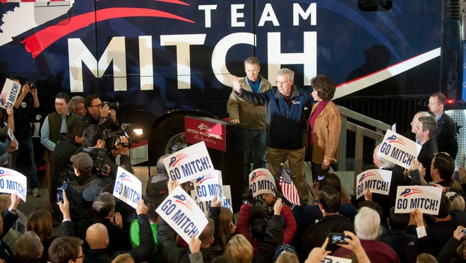 US Senators Rand Paul, left, and Mitch McConnell, center, and McConnell's wife, Elaine Chao, right, speak to supporters from a hangar in Bowman Field before the three fly around the state on the final day of the campaign. 03 November 2014