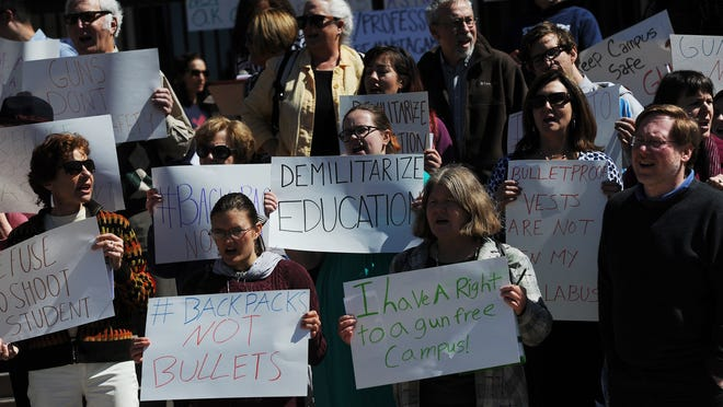"People hold signs and chant during a planned protest against the ""campus carry"" bill at the University of Nevada in Reno on March 25, 2015."