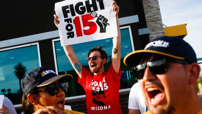 Matthew Vanek raises a sign with other protesters, activists, and fast food workers marching outside McDonalds during a demonstration for an increased minimum wage on Thursday, April 14, 2016, on 7th Street and McDowell in Phoenix, Ariz.