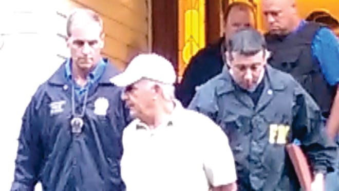 Mobster Daniel Pagano, wearing baseball cap, is led from his Cherry Lane home in Airmont on Thursday, Aug. 7 after being arrested on gambling, extortion and conspiracy charges.