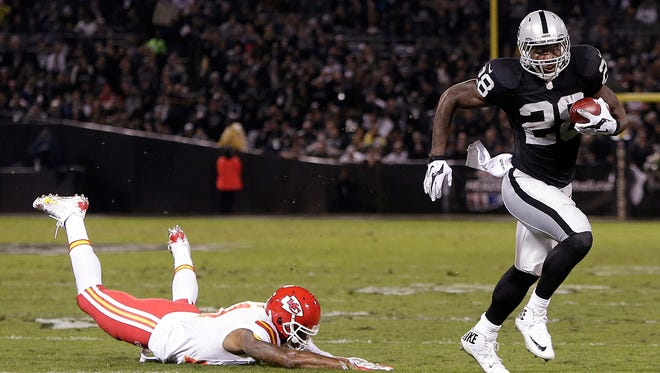 Oakland Raiders running back Latavius Murray (28) runs past Kansas City Chiefs cornerback Sean Smith on an 11-yard touchdown run during the first quarter of an NFL football game in Oakland, Calif., Thursday, Nov. 20, 2014