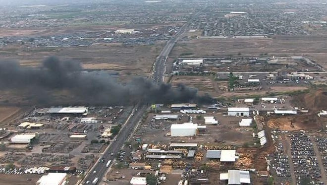 A fire at an industrial facility in southwest Phoenix sent up a large column of black smoke on May 8, 2015.