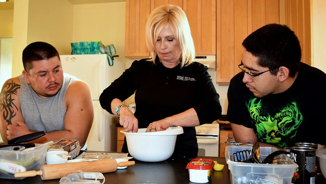 NMSU Rio Aribba County family and consumer science specialist Desaree Jimenez cuts shortening into flower while making pie dough while Brian Aquino, left, and Richie Chavez watch during a Men Making Meals cooking class at Ohkay Owingeh Pueblo.
