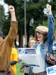 Karen Minear, right, and Ralph Marshall, left, cheer on speakers during a rally before the start of a public hearing Friday concerning the move of Harrison Medical Center from Bremerton to Silverdale.