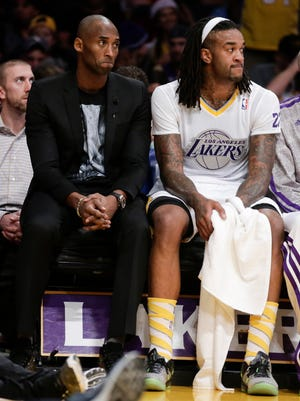 Injured Lakers guard Kobe Bryant, left, and healthy center Jordan Hill sit together during the Heat's 101-95 win Christmas Day.