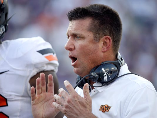 """Oklahoma State head coach Mike Gundy motivates his team in the second half of an NCAA college football game against TCU, Saturday, Oct. 18, 2014, in Fort Worth, Texas. Gundy described his team's offense as """"just very average,"""" in the 42-9 loss to TCU.  (AP Photo/Tony Gutierrez)"""