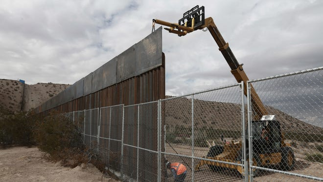 Workers raise a taller fence along the Mexico-U.S. border in New Mexico in 2016.