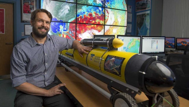 Travis Miles, with the submersible robot glider he and Greg Seroka deployed in front of superstorm Sandy in 2012. Notice the velocity sensor attached to the top of the hull.