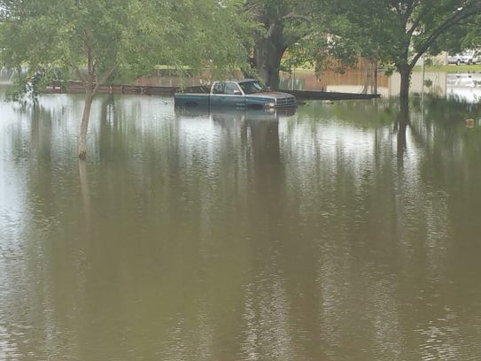 A truck is surrounded by flood water Monday in Cankton.
