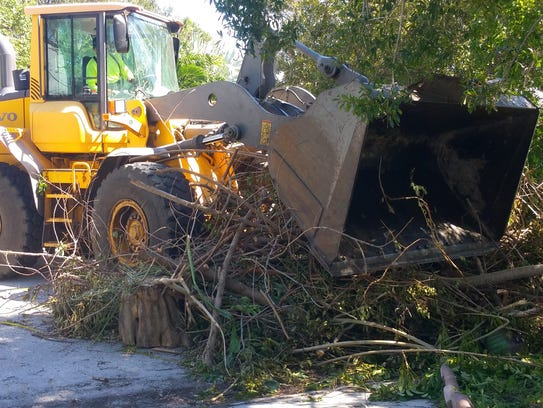 A worker uses a loader to clean up the aftermath of