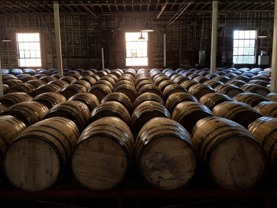 Charred oak barrels line the floor of a warehouse at