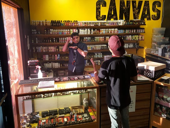 A Canvas employee shows customers a bottle of vape