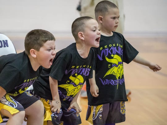 Youth wrestlers coach from the sidelines, including,