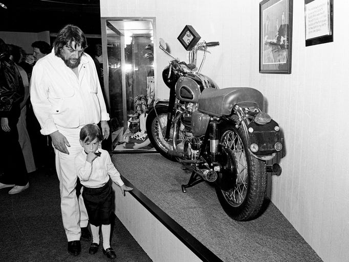 Waylon Jennings shows his 5-year-old son Shooter a motorcycle that belonged to rock 'n' roll pioneer Buddy Holly during the grand opening of his Waylon's Private Collection museum on June 12, 1984. Jennings performed in Holly's backing band in the final weeks of Holly's life.