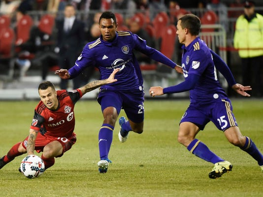 Toronto FC forward Sebastian Giovinco (10) gets tripped up by Orlando City defender Tommy Redding (29) as Orlando City defender Donny Toia (25) watches during the second half of an MLS soccer match in Toronto on Wednesday, May 3, 2017. (Nathan Denette/The Canadian Press via AP)