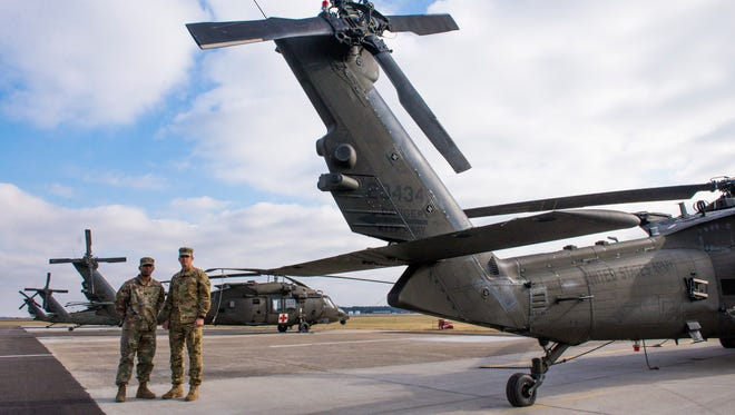 From left, flight paramedic Staff Sgt. Bala Devarajan, and First Lt. Mike Joslin, platoon leader and pilot, stand in front of HH-60 Black Hawk helicopters at Fort Campbell. Both were part of the relief effort for Hurricane Maria in Puerto Rico.