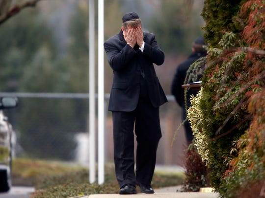 A mourner walks into a funeral service for 6-year-old Noah Pozner, Monday, Dec. 17, 2012, in Fairfield, Conn. Pozner was killed when a gunman walked into Sandy Hook Elementary School in Newtown Friday and opened fire, killing 26 people, including 20 children. (AP Photo/Jason DeCrow)