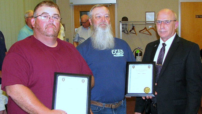 Chemung County Sewer District employees Christopher Ripley, left, and Eugene Shumway, center, join West Elmira Police Chief Peter Michalko after receiving commendations for helping recover evidence in a child porn case. Missing from the photo is employee Steve Cardamone.