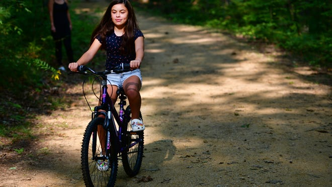 RUTLAND - After a half-day of remote learning, Gianna Smith, 11, of Rutland takes a bike ride with her mother on the Mass Central Rail Trail in Rutland State Park on Wednesday.